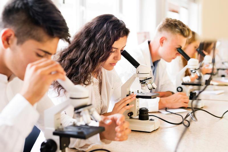 красивые-студенты-средней-школы-с-микроскопами-в-лаборатории-98863085